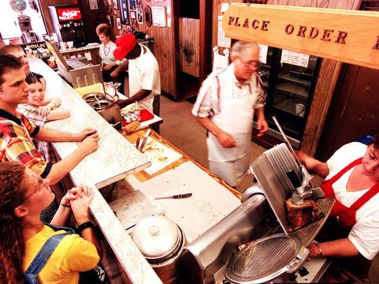 FILE 3/26/00 - Sue Cobb (background), Thomas Odom, Joe Cobb and Cathy Grace wait on customers at Joe Cobb's Bar-B-Que.