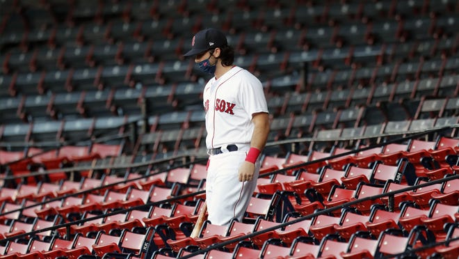 The Red Sox' Andrew Benintendi, moved from first to seventh in the batting order for Saturday night's game against the Blue Jays, walks through the empty stands before the game.