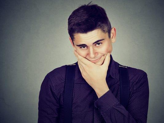 Doubtful young man posing at camera