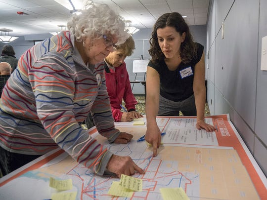 Tanya Sharon, of West Bloomfield, and Gail Whitty, of Birmingham, look to see if the proposed transit routes fit their needs. Carly Shapiro, a planner with HNTB, explains.