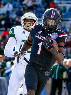 South Carolina wide receiver Deebo Samuel (1) catches a pass for a touchdown as South Florida cornerback Mazzi Wilkins (23) tries to defend during the first half of the Birmingham Bowl, Thursday, in Birmingham, Ala.