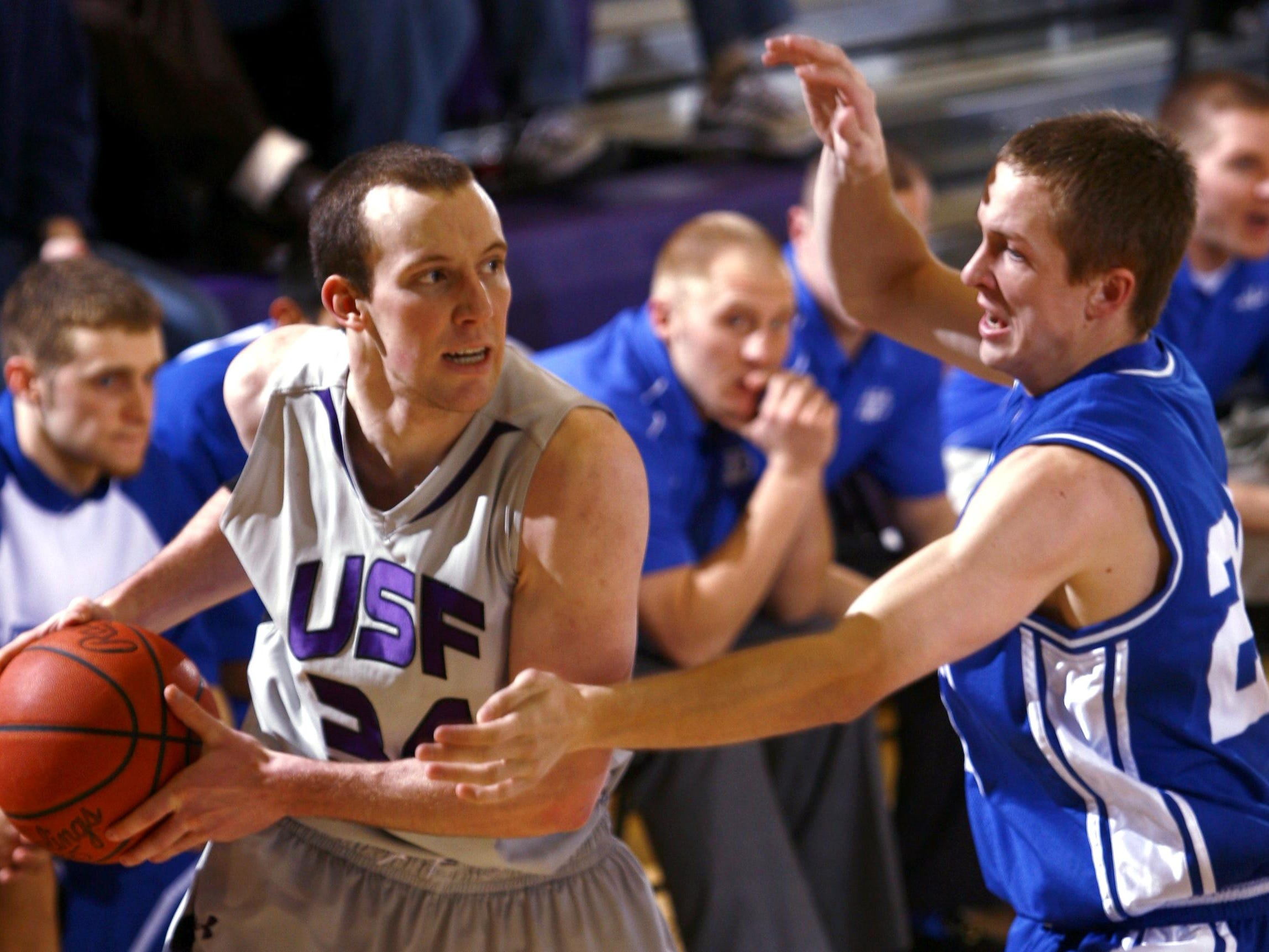 USF's David Maxwell (34) looks for a pass around Dakota Wesleyan's Chase Walder during a game at the Stewart Center in Sioux Falls, S.D., Wednesday, Feb. 2, 2011.(Devin Wagner/Argus Leader)