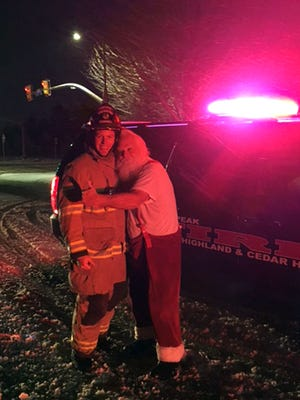 Steven Macey, right, a Santa-for-hire, from Orem, Utah gives a big hug to firefighter Capt. Danny Campbell after fire crews extinguished a fire on Macey's vehicle on Friday, Dec. 25, 2015 near Alpine, Utah. Firefighters called to the car fire in the Utah suburb got a big surprise early Christmas morning when they discovered the stranded driver turned out to be Santa Claus on the way to deliver presents.