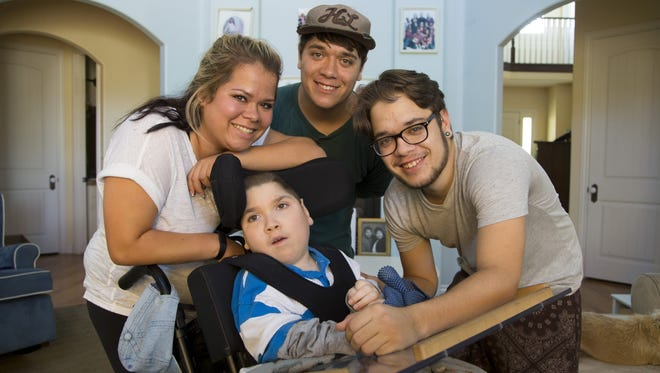 Clockwise from left: Hannah Nelson, Matthew Reed, Michael Reed and Brandon Rowin gather for a family photo. The siblings, known as the Avondale Quads, were violently abused as infants by their birth mother.