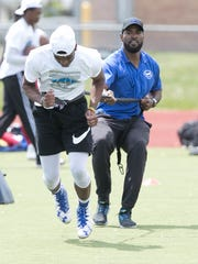 Former Detroit Lions receiver Calvin Johnson works with DaShawn Mills during the Calvin Johnson Jr. Foundation Catch a Dream football camp held at Southfield high school Saturday, May 20, 2017 in Southfield.