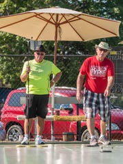 Larry Roan, President of Battle Creek Shuffleboard Club with Ken Worden (left) at Bailey Park in the Michigan State Shuffleboard Tournament on Tuesday.