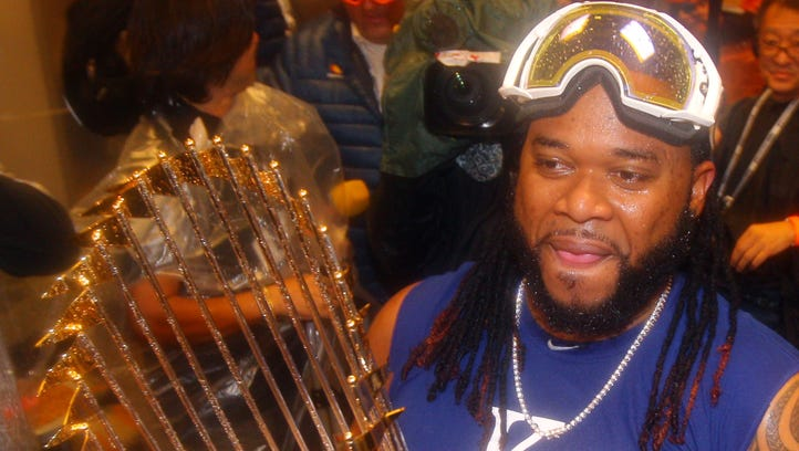 Kansas City Royals starting pitcher Johnny Cueto holds the Commissioners Trophy in the clubhouse after defeating the New York Mets to win Game 5 of the World Series at Citi Field.