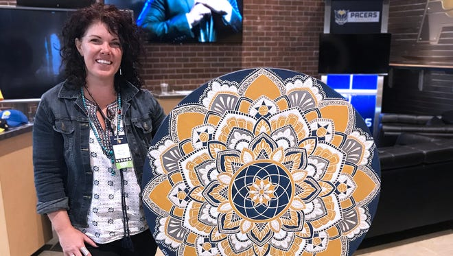 Jamie Locke, an Indianapolis artist, completed a 36-inch carved mandala in front of a crowd of basketball fans.