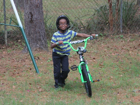 First grader Eric, the eldest of the Stringer siblings at 7, enjoys riding his bicycle.