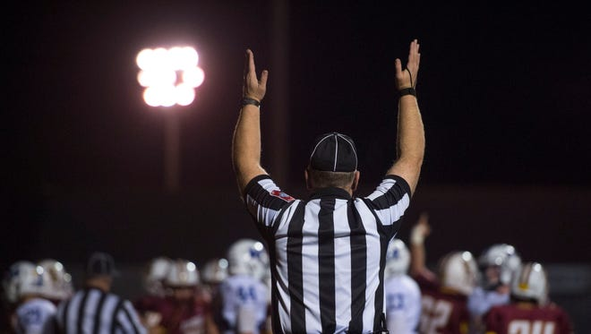 A referee signals a touchdown as the Gibson Southern Titans take on the Memorial Tigers at Gibson Southern High School in Fort Branch, Ind., on Friday, Nov. 3, 2017. High school football referees are hopeful that the fall football season will be able to be completed in its entirety while remaining safe for everyone involved.