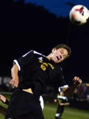 Hendersonville High senior Owen Kalada heads the ball