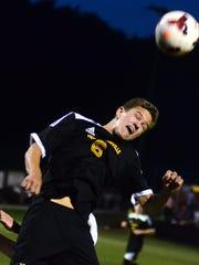 Hendersonville High senior Owen Kalada heads the ball during second-half action.