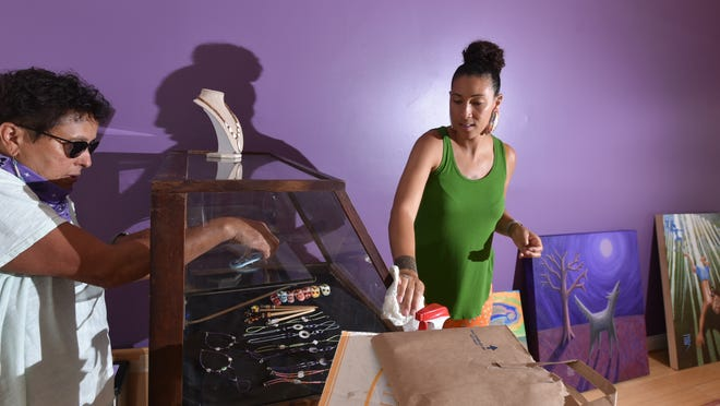 Paula Peters, left, and Danielle Hill work to set up their new shop in Mashpee Commons. The Wampanoag Trading Post will feature Native American crafts and art.