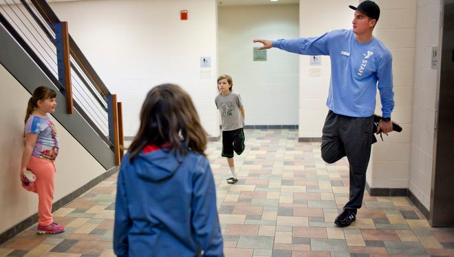 Group Fitness and Wellness Coach Dan Ochoa leads a stretching exercise during Fitness for Kids Thursday nights at the YMCA of the Blue Water Area.