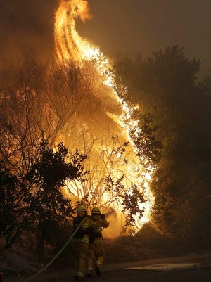 Firefighters hose down a burning tree in Santa Rosa, Calif., Monday, Oct. 9, 2017. Wildfires whipped by powerful winds swept through Northern California early Monday, sending residents on a headlong flight to safety through smoke and flames as homes burned. (AP Photo/Jeff Chiu)