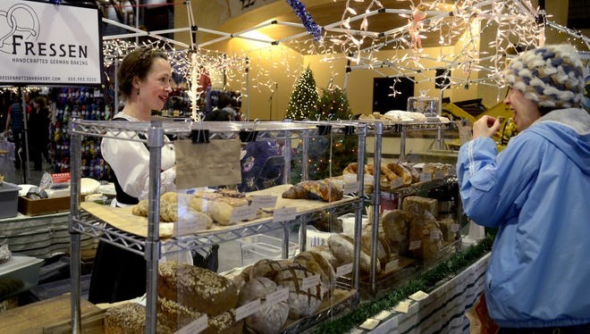 Esther Hofmeister, of Woodbury, right, tries a German baked good from Jasmine Dzikavitski, of Portland, during the Hazelnut Fest in Mount Angel, Ore., on Saturday, Dec. 6, 2014.