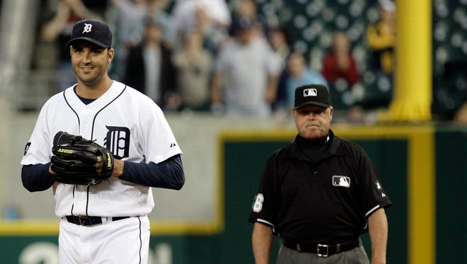 Tigers pitcher Armando Galarraga, left, smiles as he walks away from first base umpire Jim Joyce, right, who called Cleveland Indians' Jason Donald safe at first base in the ninth inning of a and lost his bid for a perfect game.