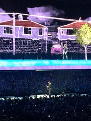 The Edge performs on the catwalk while Bono stands