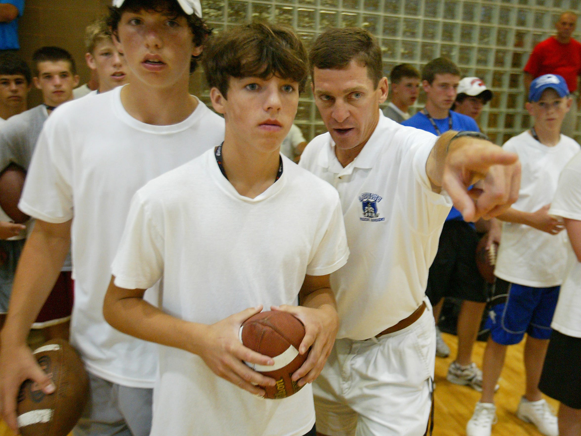 Andrew Luck, left, as an eighth grader at the Manning Passing Academy in 2004. Here, associate camp director Buddy Teevens, current head football coach at Dartmouth, instructs.