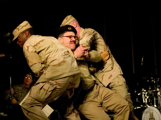Al Franken dressed as Saddam Hussein performs during the Sergeant Major of the Army  USO ( United Service Organization) Hope and Freedom tour 2005 at Camp Victory, Baghdad Dec. 21 2005.