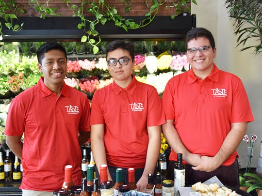 Immokalee high school entrepreneurs Eric Garcia, from left, Christopher Bances and Alfredo Villalobos Perez show off their products during a sampling event at a store.