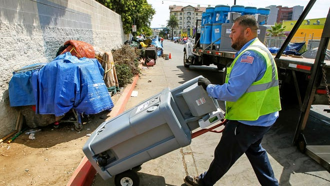 In this Sept. 1, 2017 file photo, Edwin Gonzalez from United Site Services delivers a two-station hand washing sink to the Neil Good Day Center in downtown San Diego, Calif.