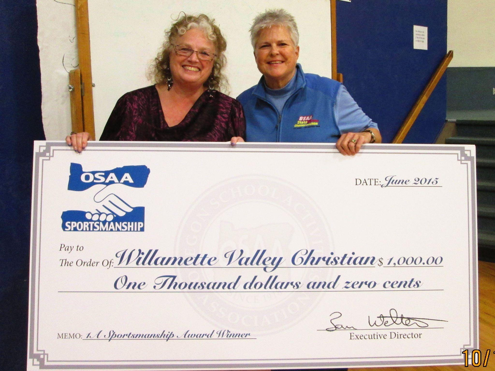 OSAA assistant executive director Cindy Simmons (right) presents a check to Willamette Valley Christian for winning the OSAA Sportsmanship Award.