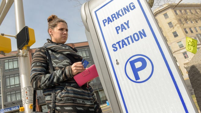 Meghan Calabro, of Middletown, uses a credit card to pay her parking fee at the corner of Cookman and Grand avenues in Asbury Park.