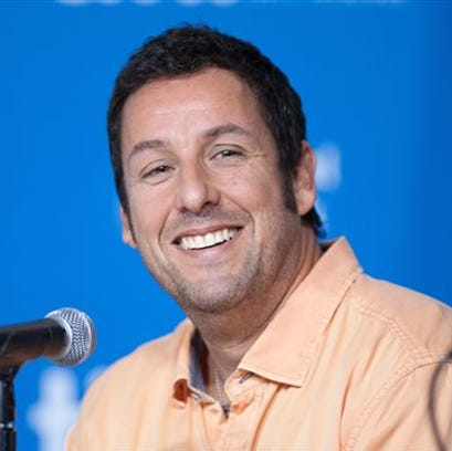 """Actor Adam Sander smiles during a press conference for """"Men, Women, and Children"""" at the 2014 Toronto International Film Festival in Toronto. Sandler has signed a deal with Netflix to star in and produce four films for the streaming service."""