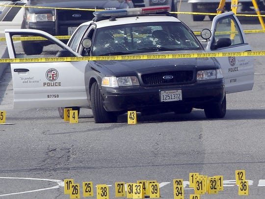 A bullet-ridden LAPD car that was attacked by killer Christopher Dorner In Corona is taped off by investigators on Feb. 7, 2013.