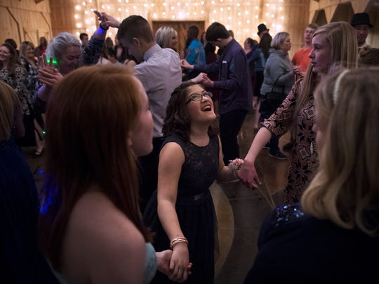 "Prom-goers hold hands as they dance Thursday, March 22, 2018, during the Union EDGE Program's annual special needs prom, ""The Royal Ball,"" at The Barn at Snider Farms in Denmark."