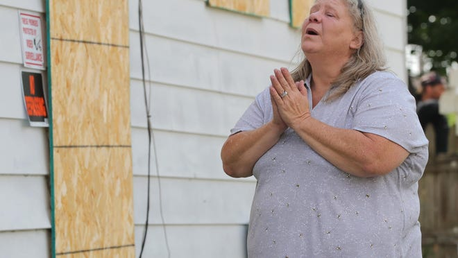 Theresa Newberry, a member of Families and Friends for a Safe Barberton, becomes emotional as she visits a boarded-up drug house Thursday in Barberton.