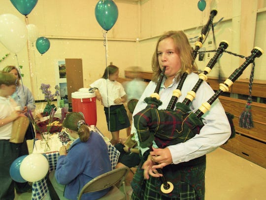 Adrienne Malcolm, a Webb High School senior, plays a bagpipe at the Scotland booth of the Euro-Fair in the school gym on May 3, 1995. Photo by Michael Patrick