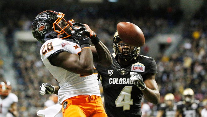 Oklahoma State Cowboys wide receiver James Washington (28) is unable to make a catch while being defended by Colorado Buffaloes defensive back Chidobe Awuzie (4) during the first half at Alamodome.