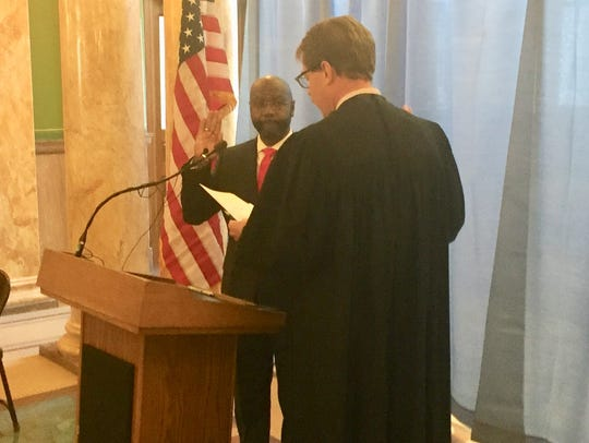 Wilmot Collins, left, takes the oath of office Tuesday to be Helena's new mayor. Judge Mike Menahan administers the oath.