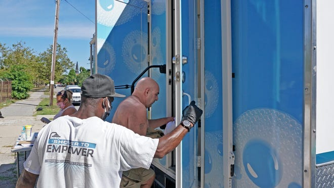 Johnnie Williams, who manages the Shower to Empower program, holds the door for Rod Point, as he enters one of the showers on the truck Friday.