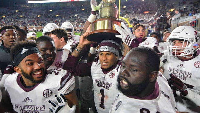 Mississippi State  players celebrate with the Egg Bowl trophy after beating Mississippi.