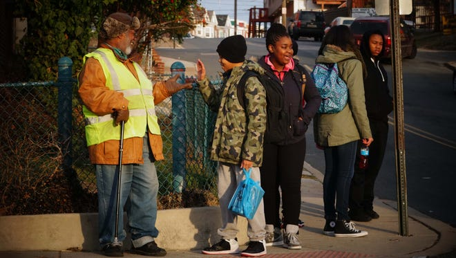 Volunteer crossing guard Earl Tate stands on the corner of 26th and Jessup Street, and plays a hand slapping game with David Thompson as he waits for his school bus.