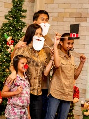 In this file photo, Brigitte, Arnel and Caerah Bonto pose for a family picture at the annual Breakfast With Santa last year using fun props.