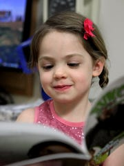 A child reads a book as part of the Reach Out and Read