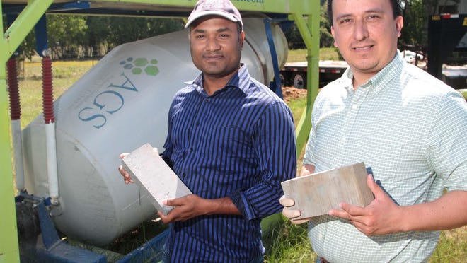 Rashed Islam, left, engineer, and Carlos Montes, CTO, of Alchemy Geopolymer Solutions pose with their product by one a concrete mixers where they mix geopolymers.