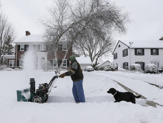 Ernie Swanson snow-blows his neighbor's sidewalk with