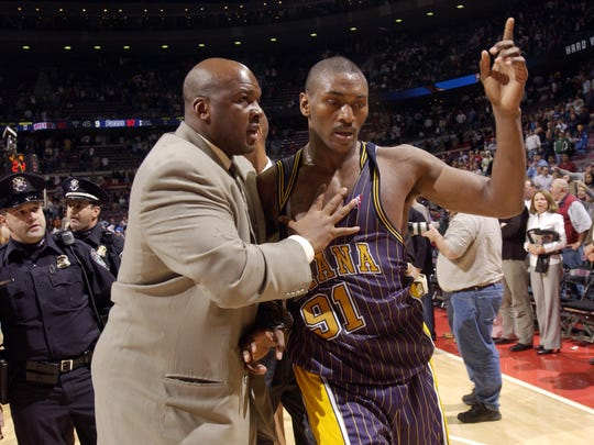 Pacers' assistant Chuck Person (left) is shown leading Ron Artest, after a brawl near the end of the game against the Detroit Pistons in Auburn Hills, Mich., on Nov. 19, 2004 .