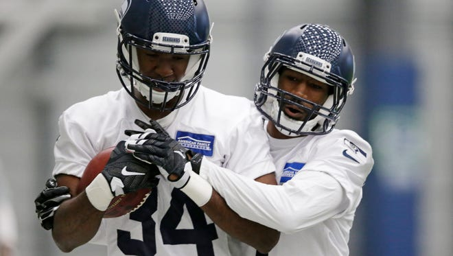 Seattle Seahawks' Denzel Thompson, left, is grabbed by DeAndre Elliott during a rookie minicamp workout Sunday, May 8, 2016, in Renton, Wash. (AP Photo/Elaine Thompson)