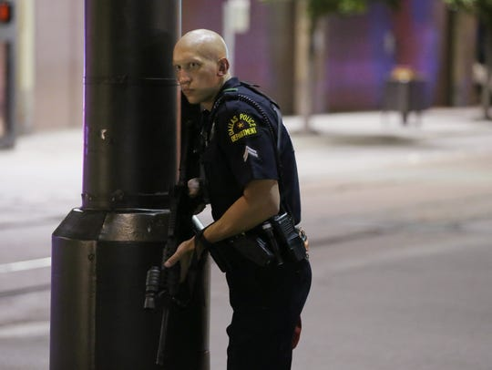 A Dallas policeman keeps watch on a street in downtown