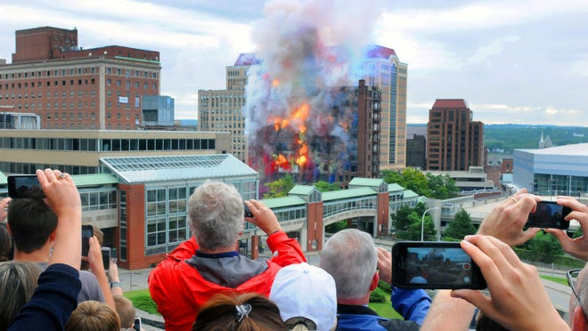 Spectators watch from the Empire State Plaza as the Wellington Annex is imploded to make way for the new Capital Center on Saturday in Albany.