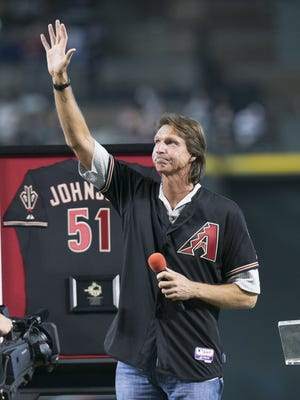 MLB Hall of Fame pitcher Randy Johnson waves to the crowd during a ceremony to retire his #51 jersey at Chase Field in Phoenix before the MLB game between the Diamondbacks and the Reds on August 8, 2015.