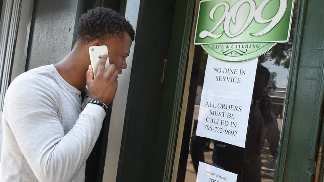 Marquis Francis looks at the signs on the door as he calls in his lunch order outside Cafe 209 in Augusta, Ga., Wednesday afternoon June 3, 2020.