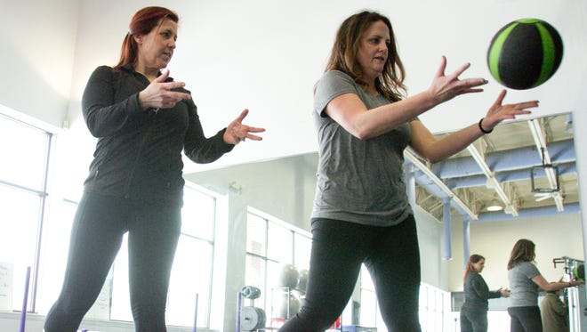 Pure Fitness Performance Training owner/trainer Keri McCartney, left, works with new client Heather Kufahl on her mobility by having Kufahl rotate from a sideways stance to throw a ball against a wall to her left and catch it.