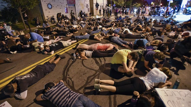 Demonstrators lie in the street Thursday at the site where Daniel Prude was restrained by police in Rochester, New York. Seven police officers involved in the suffocation death of Daniel Prude in Rochester were suspended Thursday by the city's mayor, who said she was misled for months about the circumstances of the fatal encounter.
